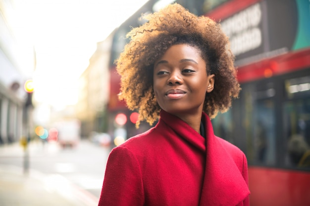 赤いコートを着て、通りを歩いてビジネス女性