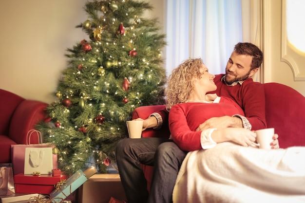 ソファに横たわって、一緒にクリスマスを祝う素敵なカップル