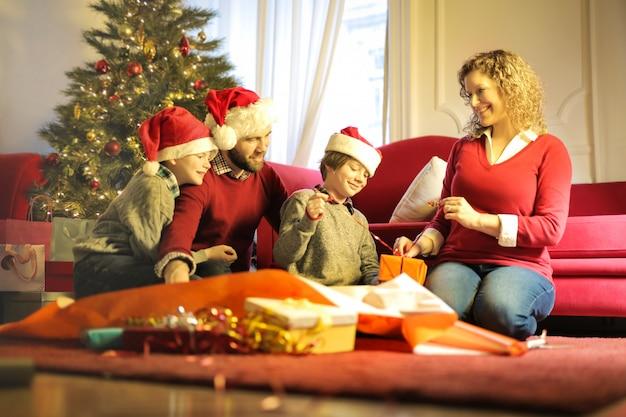 Семья весело проводит время вместе, открывая рождественские подарки