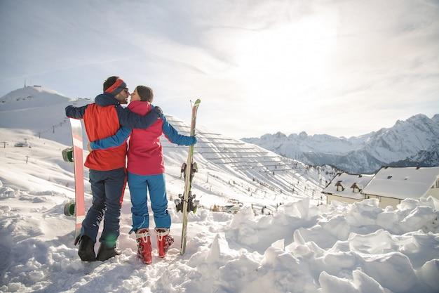 山でスキーを楽しんでいる素敵なカップル