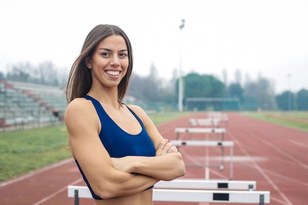Красивая спортивная женщина тренируется на спортивной площадке, на беговой дорожке