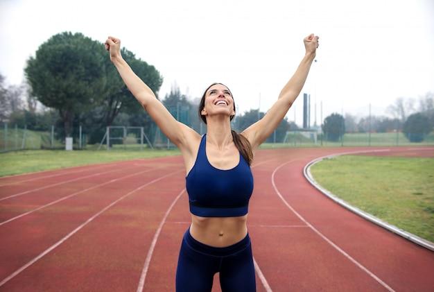 Спортивная женщина празднует свое удовлетворение после бега на спортивной площадке