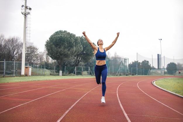 Спортсмен бежит по беговой дорожке на открытом воздухе