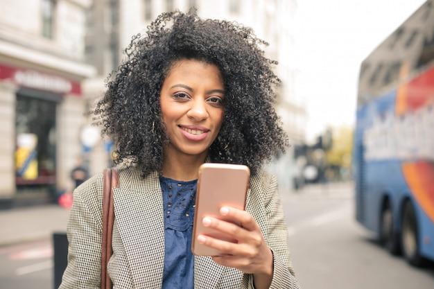 通りを歩いて、彼女の電話をチェックする美しい女性