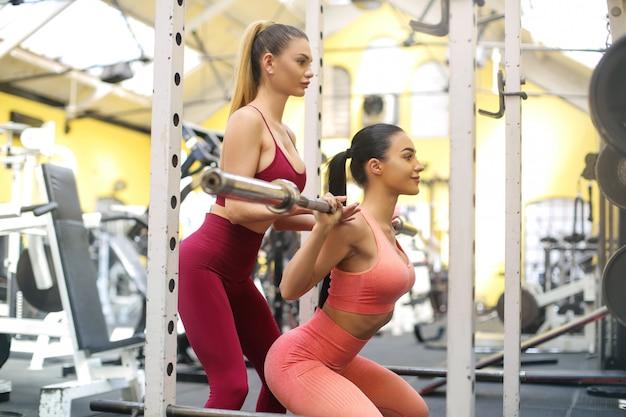 Девушка тренируется в тренажерном зале с личным тренером