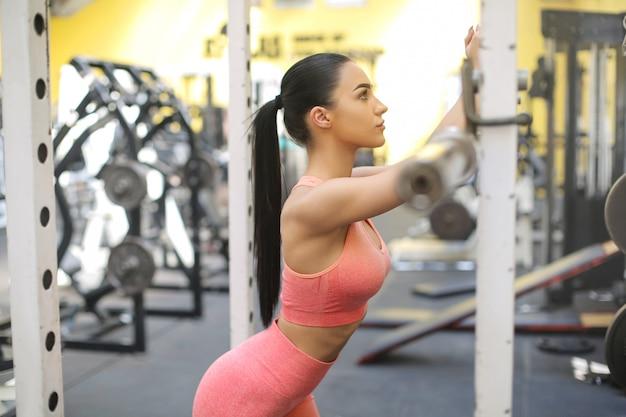 美しい女性は、ジムでハードトレーニング