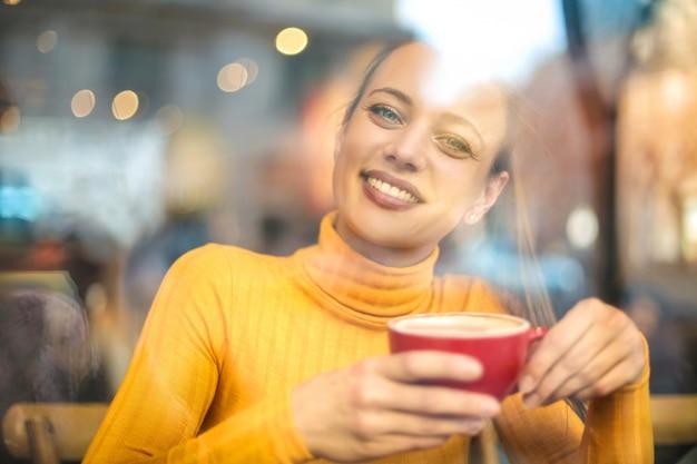 Красивая девушка пьет что-то горячее в баре