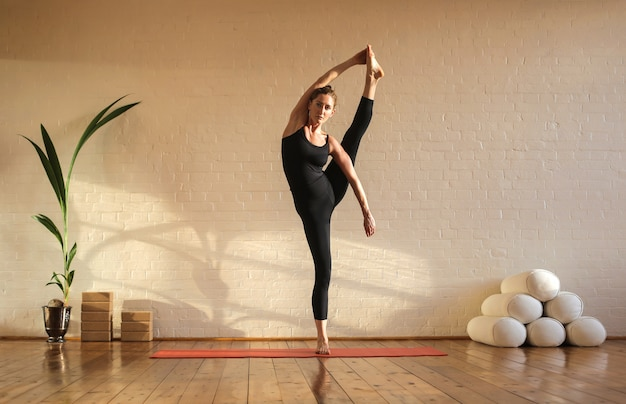 柔軟な女の子がスタジオでヨガを練習