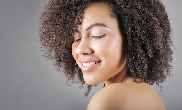 Красивая афро-американских женщина, заботясь о ее вьющиеся волосы