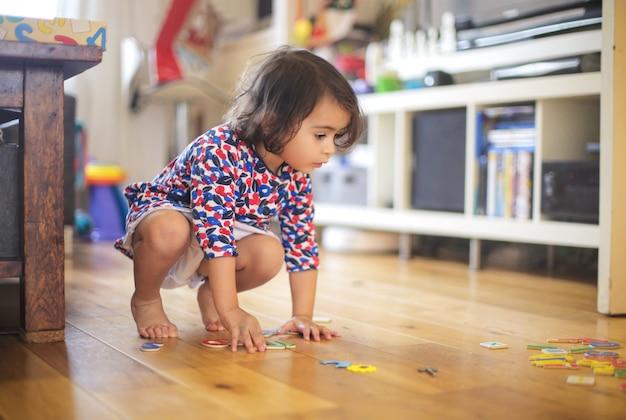 Милая девушка играет с настольную игру у себя дома