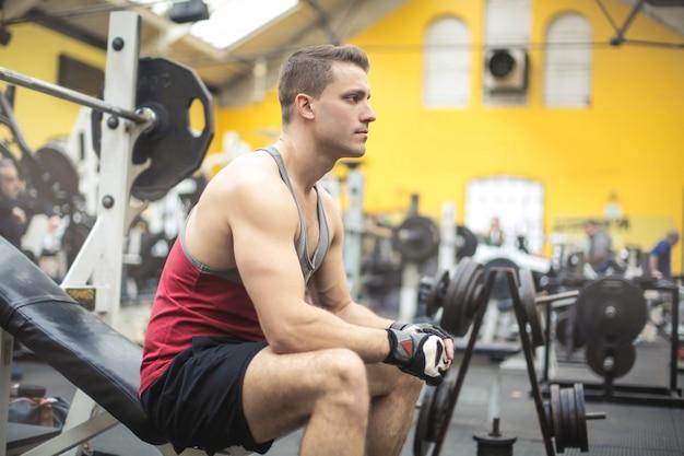 Привлекательный мужчина отдыхает после тренировки вряд ли в тренажерном зале