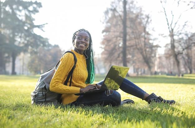 ラップトップを使用して、公園に座っているきれいな女性
