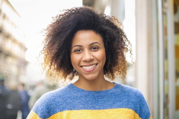 通りを歩きながら笑っている陽気な若い女性