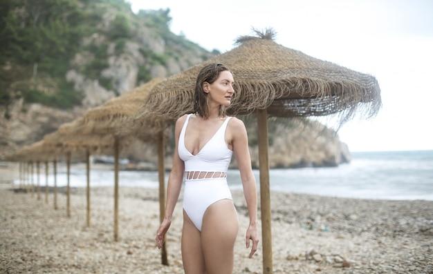嵐の日にビーチを歩いて美しい女性