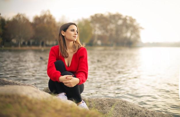 リラックスして、湖の隣に座っている女の子