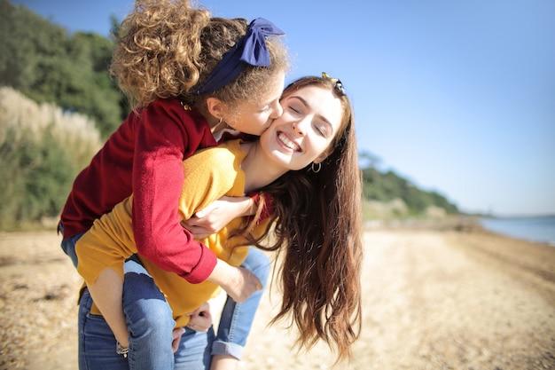 Сладкая мама с дочерью на спине белые прогулки на пляже