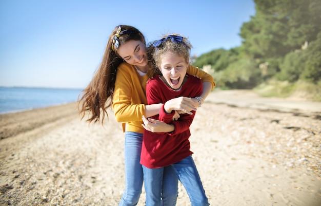 Мать щекочет дочь, играя на пляже