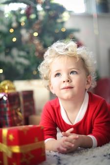 Красивый ребенок сидит на ковре, в окружении рождественских подарков