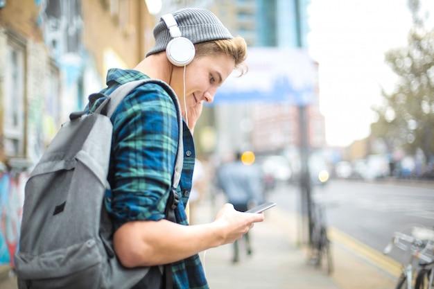 Парень слушает музыку в наушниках во время прогулки по улице