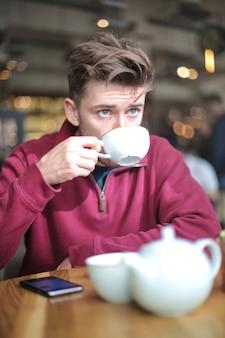 Мужчина сидит в кафе, пьет чай