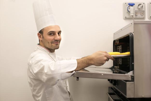 Шеф-кондитер кладет печенье в духовку