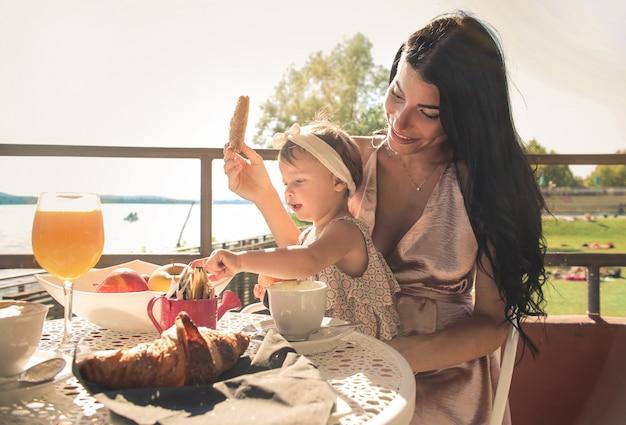 彼女の赤ちゃんと一緒に朝食を持っている甘いママ
