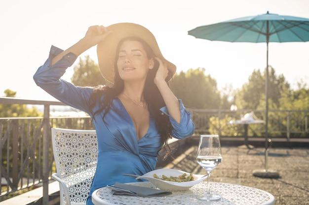 Красивая очаровательная женщина обедает на террасе