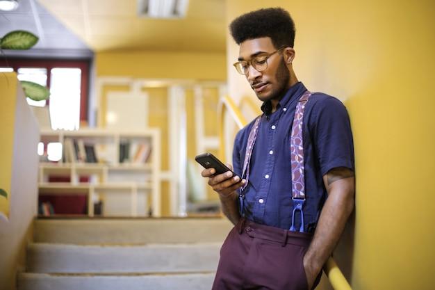 事務所に立っている彼のスマートフォンをチェックする代替の男