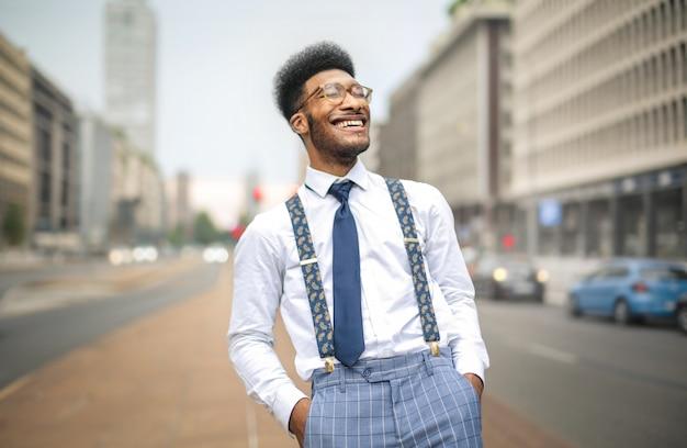 通りを歩きながら笑っているスタイリッシュな男