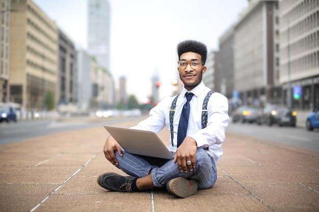 Красивый мужчина сидит на улице, работает со своим ноутбуком