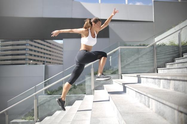 階段の上を実行している陽気な女性