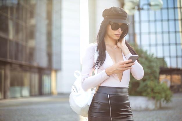 通りを歩いて、彼女のスマートフォンをチェックする女の子