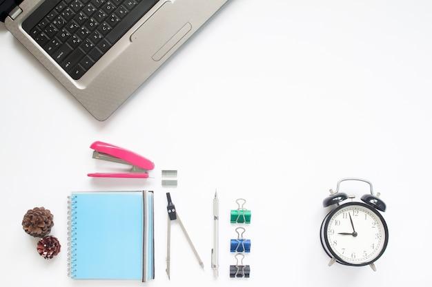 ラップトップコンピュータと文房具と目覚まし時計付きの作業スペースの創造的な平らなレイアウト