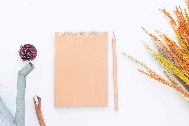 白い背景にクラフトノートブックと秋の概念の創造的なフラットなレイアウト