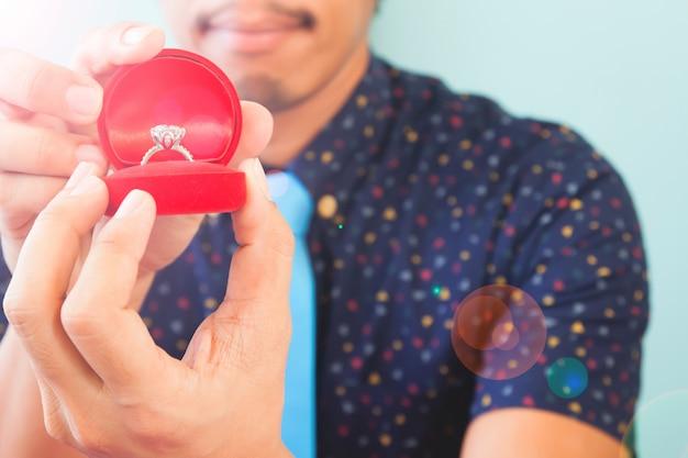 ダイヤモンドリングの箱、愛と結婚式の概念を保持しているアジアのひげのある男