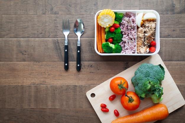 健康的なランチボックスのクリエイティブな平らなレイ、焼いた鶏の胸、栄養食品