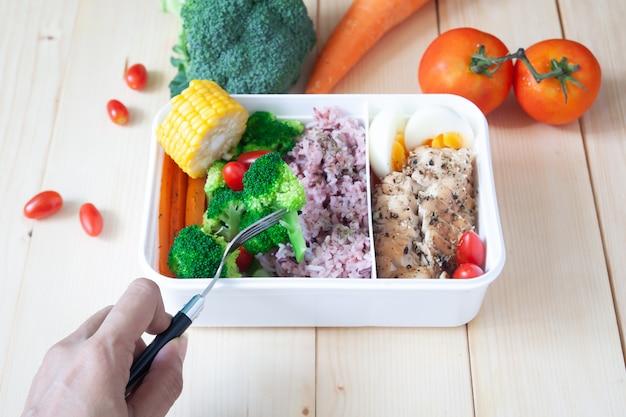 女性の手、フォークを使って健康的なランチボックスを食べる、グリルした鶏の胸肉、ゆで卵