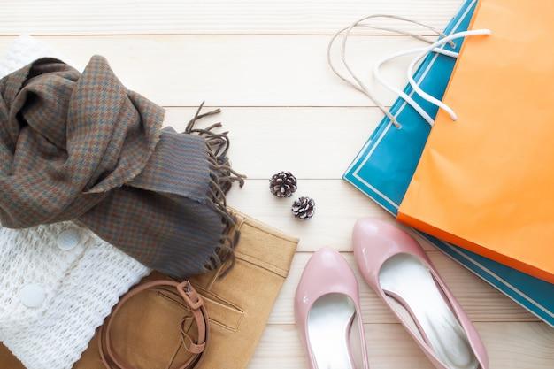 秋の流行のファッション、女性の服とショッピングバッグ、フラットは木製の背景に置く