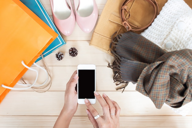 女性の手は衣類やアクセサリーと携帯電話を使用して、トップビュー、秋のショッピング