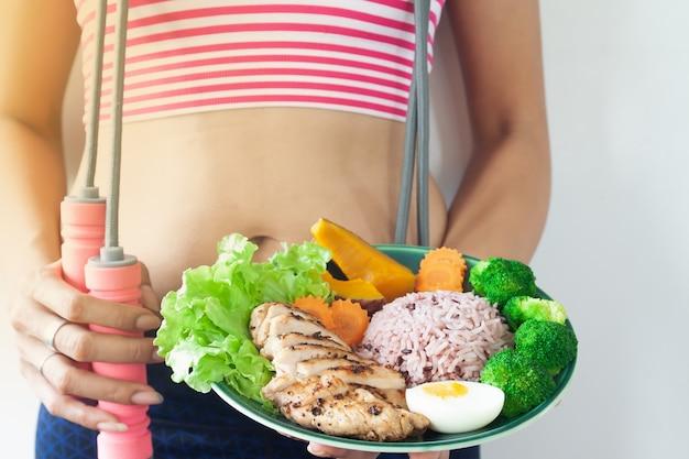 健康的な食べ物のプレートを保持しているスポーツ器具とフィットネス女性