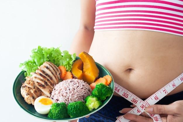女性、腹、脂肪、スポーツ、ブラジャー、健康的な食べ物の料理を保持しているテープを身に着けている