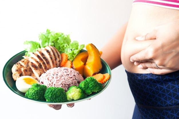 健康的な食べ物のプレートを保持する腹の脂肪を持つ女性