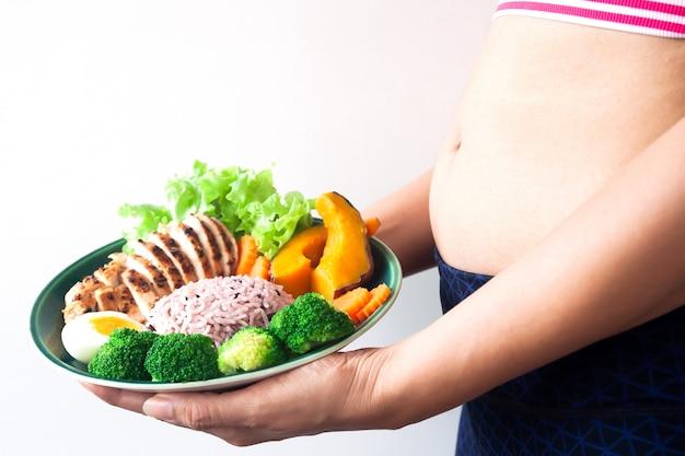 健康的な食べ物、ライスベリーと野菜とフィットネス女性の手に野菜とグリルした鶏の胸