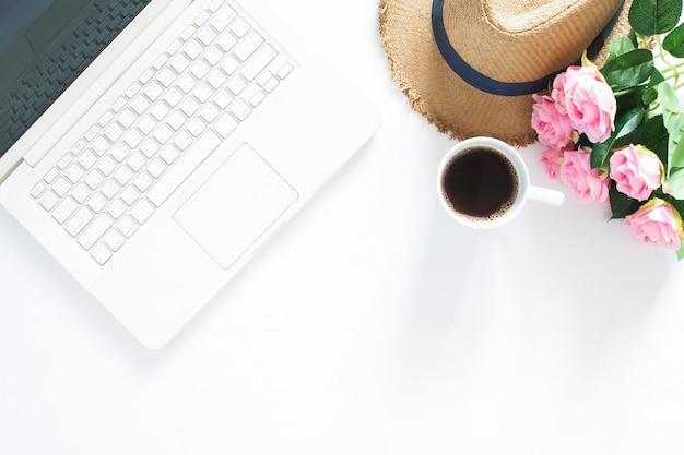 カジュアルな帽子、コーヒーとピンクのバラのカップ、コンピュータのラップトップのフラットなレイアウトは、コピースペースと白い背景でトップビュー