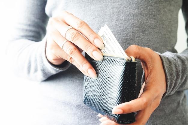 Женщина руки, проведение доллара сша законопроекты в небольшой кошелек. концепция экономии денег