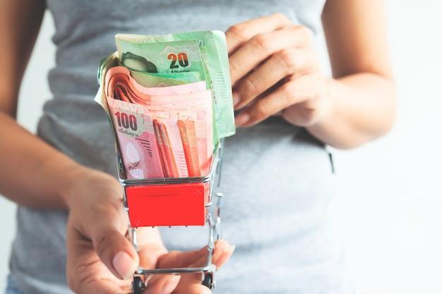 Женщина, держащая тележку с тайскими банкнотами, бизнес и финансы