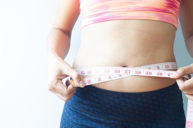 身体を測定するスポーティーな女性は、腹の脂肪を取り除く。健康的なコンセプト