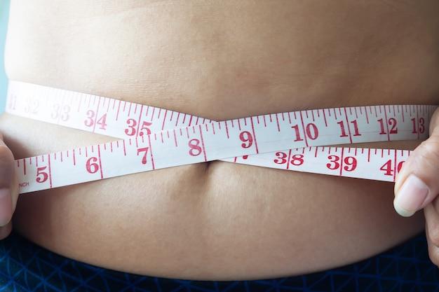ウエストを測定する女性のショットを閉じて、ダイエットの概念