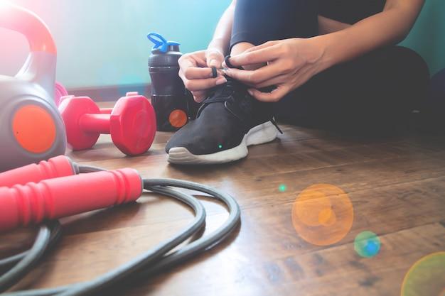 靴を結ぶフィットネス女性、自宅でのトレーニング