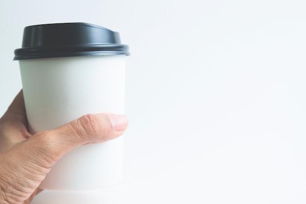女の手は、ホットドリンクのカップを持って、白い背景に閉じます